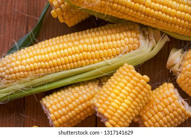 Fresh corn on cobs on rustic wooden table, closeup flat lay, top view. Ripe corn. Half of broken open sweet corn. Flat lay, top view
