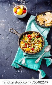 Fresh corn and tomato succotash with lima beans, sage and bacon on a dark wooden surface.