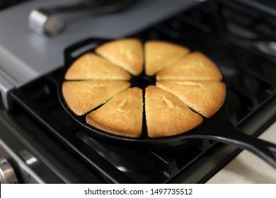 Fresh cornbread from the oven baked in a cast iron wedge pan, resting on top of the stove.