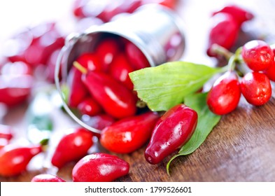 fresh cornus on the wooden table, red cornus