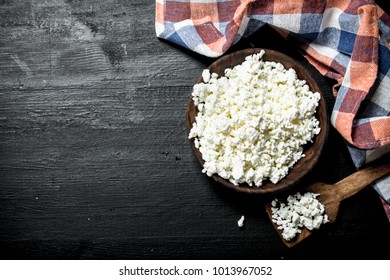 Fresh cottage cheese in a bowl. On the black chalkboard.