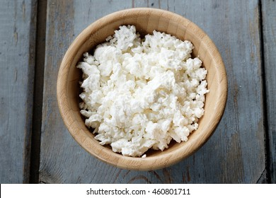 Fresh cottage cheese in bowl on wooden table
