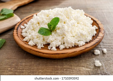 Fresh cottage cheese with mint leaves in wooden plate on wooden background.