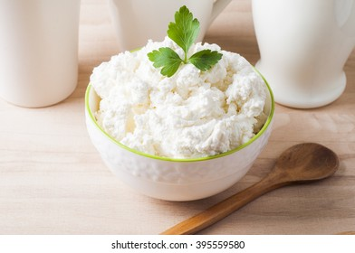 Fresh cottage cheese in a white bowl on a wooden table