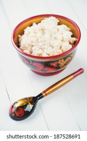Fresh cottage cheese in a wooden khokhloma bowl, vertical shot