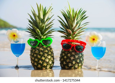 Fresh couple pineapples with sun glasses and cocktail glasses on clean sand beach with sea wave background - fresh fruit and drink with sea sand sun vacation background concept