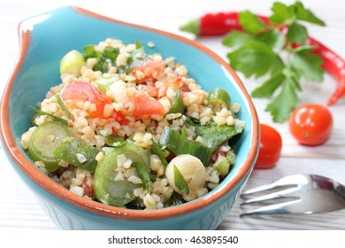 fresh Cous Cous Salad with tomatoes, spring onions, chillies and parsley in a small blue bowl on a wooden grey table with ingredients around