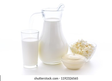 Fresh cow milk in a glass on a white background with a useful curd and sour cream on a white background. Delicious dairy products.