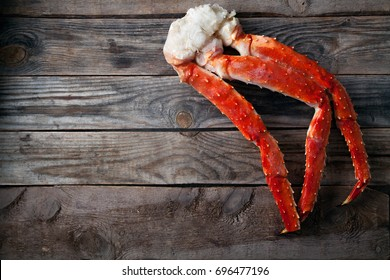 Fresh crab claws on vintage wooden background. Horizontal composition. Copy space for banner.