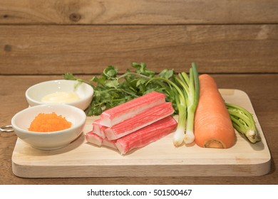 Fresh Crab Stick with shrimp eggs and vegetable preparing on a wood block in Front Till Shot