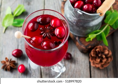Fresh cranberry juice with cinnamon and anise in glass jars on the old wooden background. Selective focus.Top view.