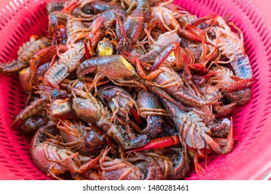 Fresh crayfish with a head turned off in a purple basket