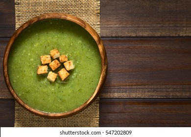 Fresh cream of zucchini soup with croutons in wooden bowl, photographed overhead on dark wood with natural light (Selective Focus, Focus on the soup)