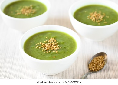 Fresh cream of zucchini soup with toasted sesame seeds on top served in bowls, photographed with natural light (Selective Focus, Focus in the middle of the first soup)