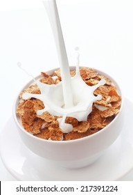Fresh creamy milk splashing into a bowl of tasty flavored chocolate cereal flakes for a delicious breakfast and energizing start to the morning