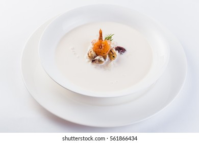 Fresh Creamy seafood soup with shrimps on a white plate on a light background (close)