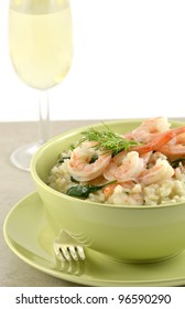 Fresh and creamy Shrimp and Spinach Risotto in green bowl closeup with glass of white wine, vertical format