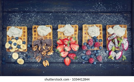 fresh crispy waffles with fruits and whipped cream on dark board