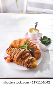 Fresh Croissant with berries and cup of coffee for breakfast, suculent flowers on white wooden stone , copy space