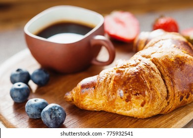 Fresh croissant, coffee cup and berries