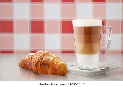 Fresh croissant and coffee on white table.