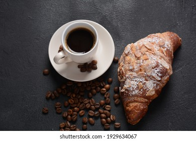 Fresh croissant with a cup of coffee, roasted beans on vintage background