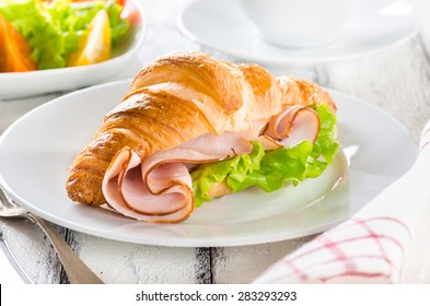 Fresh croissant with ham and salad leaf with fresh salad on white
