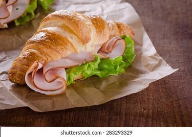 Fresh croissant with ham and salad leaf on dark wooden background