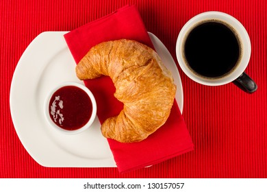 fresh croissant with marmalade and coffee