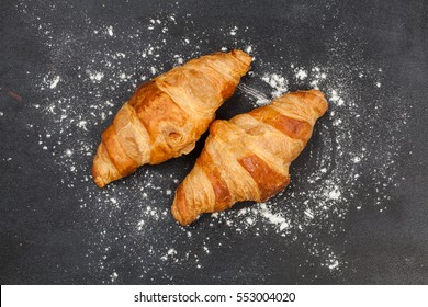 Fresh croissant on a black slate background. Top view