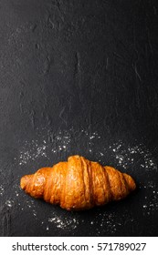 Fresh croissant on a black slate background. Top view . Copy space