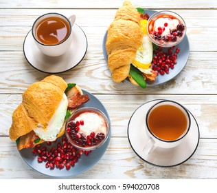 Fresh croissant  with orange yolk fried egg, bacon, spinach and cheese, homemade yogurt with cherry syrop, pomegranate and cup of tea for breakfast. Horizontal view. Continental breakfast concept