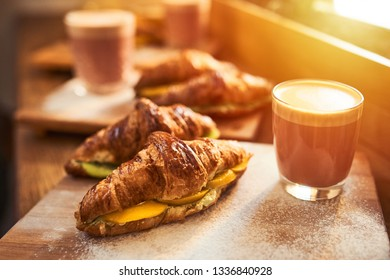 Fresh croissant and original authors coffee on beet milk with fruits on wooden plate on table. Healthy breakfast food concept. Traditional french lunch in morning cafe with gold sunlight flare.
