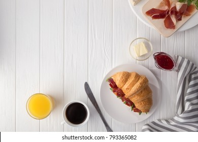 Fresh croissant sandwich with ham, cheese and arugula on white wooden table. Croissant breakfast. Free space for text. Served with coffee, cheese, ham, orange juice, jam. View from above. Top view.