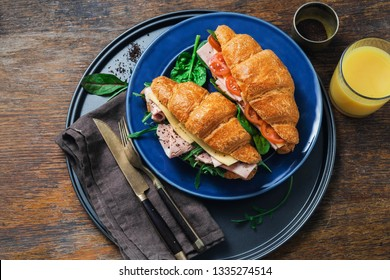 Fresh croissant sandwiches with orange juice on wooden table