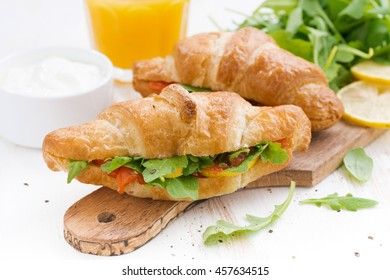 fresh croissant stuffed with fish and arugula for breakfast on wooden board, horizontal