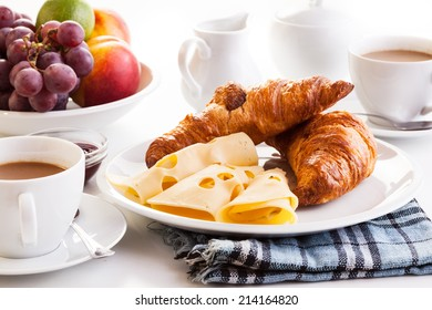 Fresh croissants with cheese, fruits and coffee