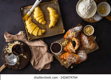 Fresh croissants with chocolate on a dark stone background top view