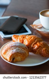 Fresh croissants, a cup of cappuccino and digital gadjets on a working table. Coffee break or business breakfast concept.