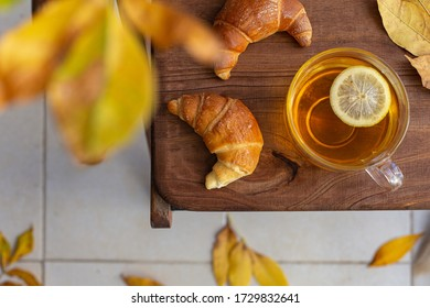 Fresh croissants and a Cup of tea with lemon on a wooden table in the garden in autumn. Top  view