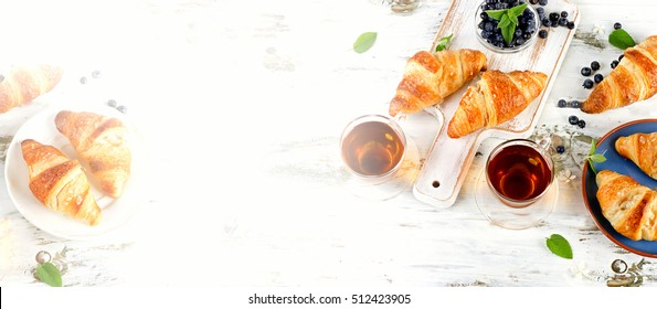 Fresh Croissants with Glass Cups of Black Tea for  Breakfast. Top view. Banner