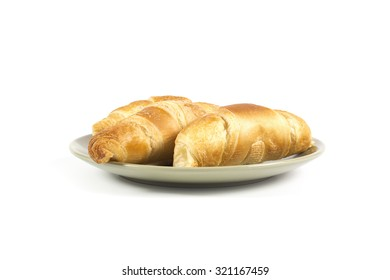 Fresh croissants on green plate isolated on white