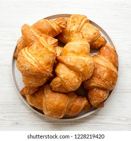 Fresh croissants on grey round plate on white wooden table, overhead view. From above, flat lay, top view.