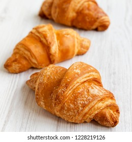 Fresh croissants on white wooden table, side view. Selective focus.