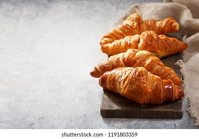 fresh croissants on wooden board, with copy space