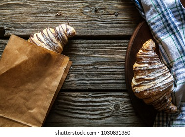 Fresh croissants in paper bag on wooden background. Food, flour, breakfast, pastry
