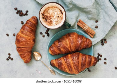 Fresh croissants, together with espresso coffee on a blue background. The view from the top