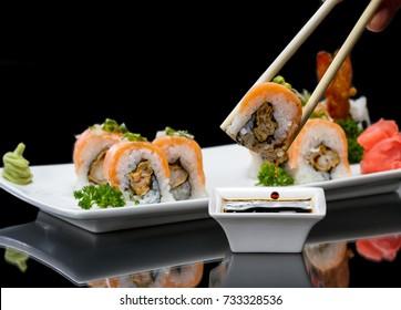 fresh crunchy fried shrimp sushi roll isolated on a black background