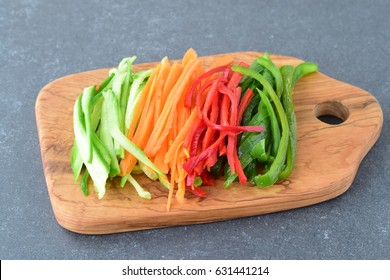 Fresh cucumber, carrot, red and green sweet paprika sliced in stripes on an olive wood cutting board on a grey abstract background. Step by step cooking