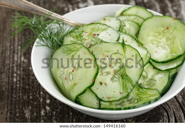 Fresh cucumber salad in bowl on wooden board